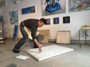 Artist in the studio preparing painting